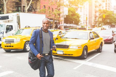 Photo for Black man crossing a street in New York. Young man wearing smart casual clothes commuting in the city, with buildings and cars on background. Commuter lifestyle and youth culture concepts. - Royalty Free Image