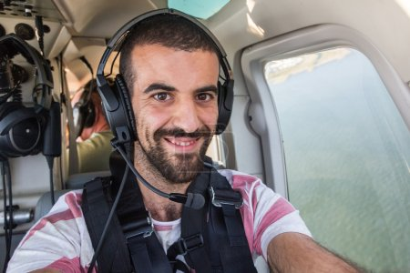 Young Man Taking Selfie in Helicopter Cabin While Flying