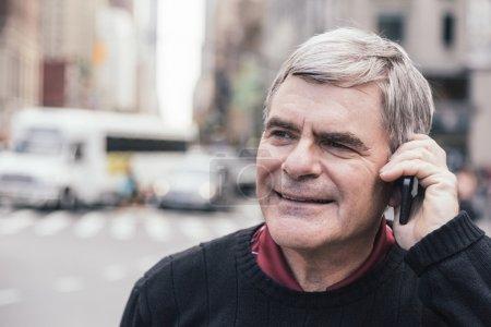Senior Man Talking on Mobile Phone in New York...
