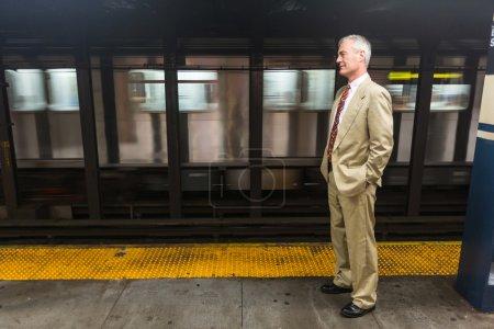 Senior Businessman Waiting for the Train at Subway Station