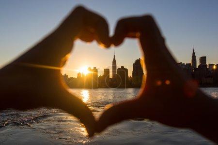 Photo pour Mains au coucher du soleil, skyline de new york sur fond en forme de coeur - image libre de droit