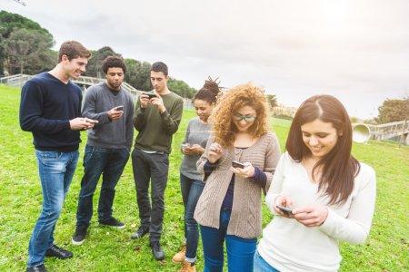 Photo pour Multiethnique groupe d'amis, téléphone intelligent accro - image libre de droit