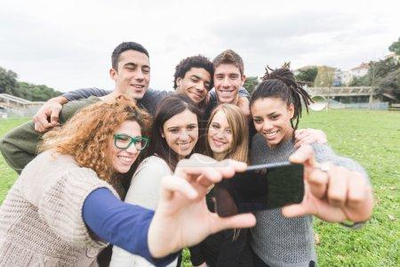 Photo pour Groupe multi-ethnique d'amis prenant Selfie au parc - image libre de droit