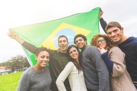 Photo pour Groupe multiethnique d'amis avec le drapeau brésilien - image libre de droit