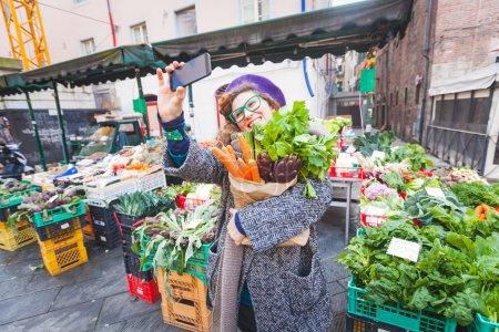 Photo pour Jeune femme prenant un selfie au marché aux légumes - image libre de droit