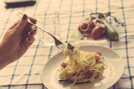 Hand with spaghetti on fork