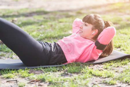 Young Woman Doing ABS Exercises at Park.