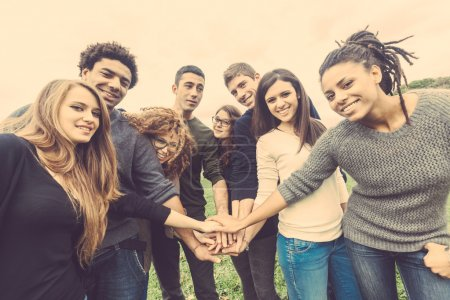 Multiracial group of friends with hands in stack