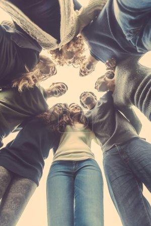 Photo pour Groupe multiracial d'amis embrassés dans un cercle, concept fort sur le travail d'équipe et la coopération, se réfère également à l'immigration et l'amitié . - image libre de droit
