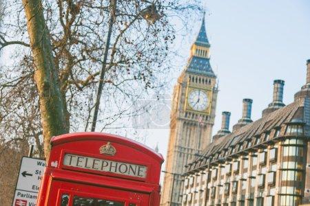 Photo pour Boîte de la célèbre téléphone rouge avec Big Ben sur fond dans un morningin début ensoleillé Londres. Il y a aussi certaines cheminées et arbres. - image libre de droit