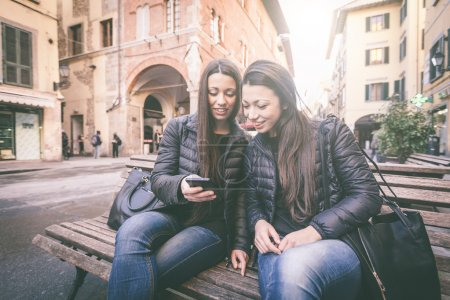 Photo for Two female twins looking at a smart phone. They wear black jackets and jeans. Urban scene with houses and street on background. - Royalty Free Image
