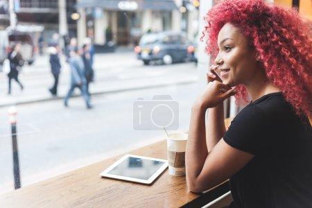 Photo pour Belle fille aux cheveux roux bouclés parlant sur un téléphone intelligent dans un café. Aussi elle tient une tasse de café et elle a une tablette numérique sur la table . - image libre de droit