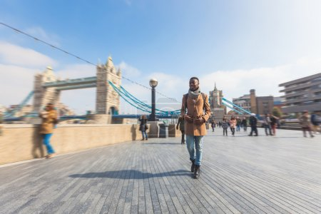 Man walking in London on Thames sidewalk, with Tow...