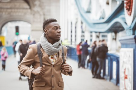 Photo pour Young black man in London walking  on Tower Bridge. He wears a brown coat and light blue jeans. Traffic and other persons on background. - image libre de droit