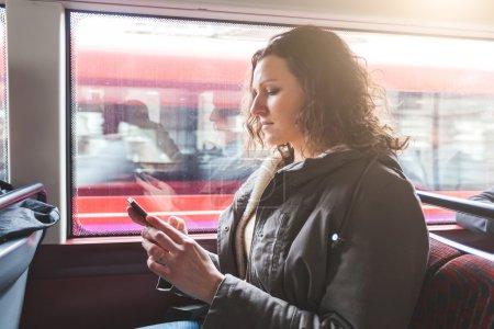 Photo pour Belle femme tapant sur le téléphone intelligent tout en faisant la navette à Londres avec le bus à deux étages. Elle est assise à côté de la fenêtre avec des bâtiments et de la circulation sur le fond . - image libre de droit