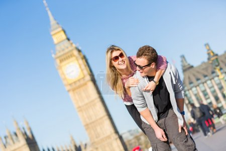 Happy young couple enjoying a piggyback ride in London