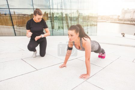 Woman doing push-ups exercises with her personal trainer