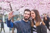 Hipster pár s selfie ve Stockholmu s Třešňové květy