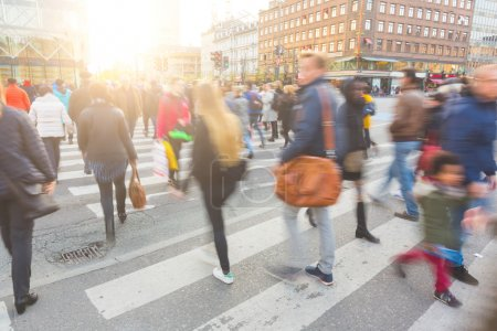 Photo for Blurred crowd of people walking on zebra crossin in Copenhagen in late afternoon. Some of them also bring a bike, typical mode of transport in the city. - Royalty Free Image