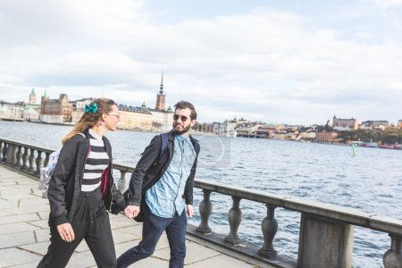 Young hipster couple running hand in hand in Stockholm