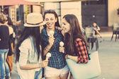 Tři šťastné ženy jíst zmrzlinu ve městě