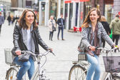 Two women going by bike in Copenhagen.