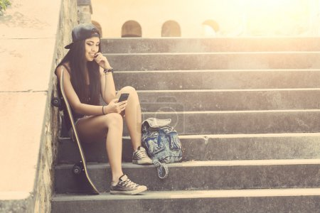 Portrait of a beautiful skater girl looking at smart phone