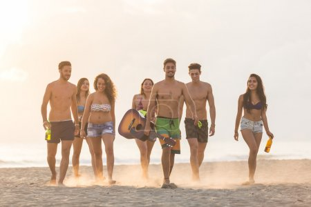 Group of friends walking on the beach at sunset.
