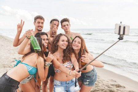 Multiracial group of friends taking selfie on the beach