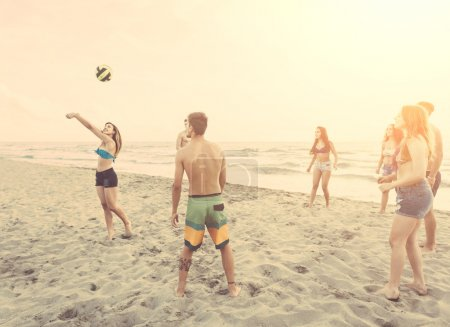 Group of friends playing with ball on the beach