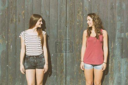 Portrait de deux belles filles avec fond en bois