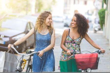 Photo for Multiracial couple of friends riding bikes on the street. They are two women wearing summer clothes and walking on a small street with their bikes. They are bringing some shopping bags. - Royalty Free Image