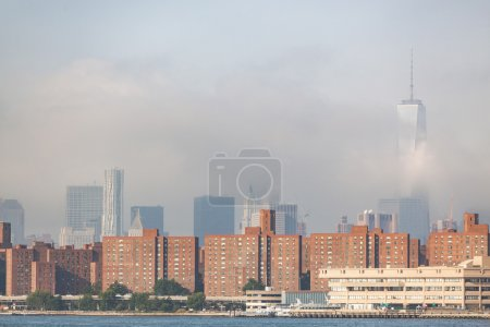 Photo for Residential buildings in New York with modern skyscrapers on background, partially covered by fog. Photo taken in the early morning from East River coast - Royalty Free Image