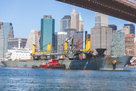 Photo pour Vraquier passant sous le pont de Brooklyn à New York et naviguer vers le nord sur l'East river. Sur le fond il y a downtown Manhattan avec quelques gratte-ciels. - image libre de droit