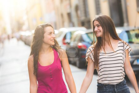Two girls walking on the street. They are two youn...