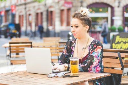 Girl working on her computer outdoor.