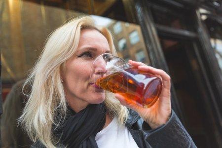 Beautiful woman enjoying a pint of beer in London