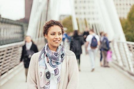Young mixed race woman walking on a bridge in London