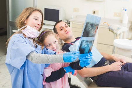 Little dentists looking at x-ray of adult patient