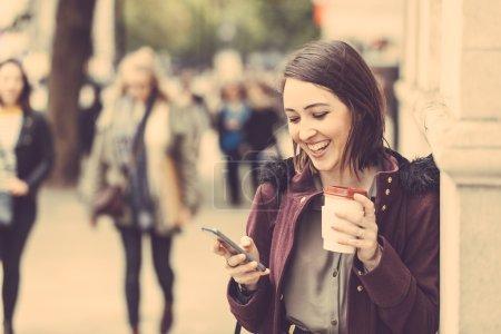 Photo pour Une jeune femme à Londres debout sur le trottoir, tenant une tasse de thé et tapant sur son téléphone intelligent. C'est une journée d'hiver nuageuse, et il y a beaucoup de personnes floues sur le fond . - image libre de droit