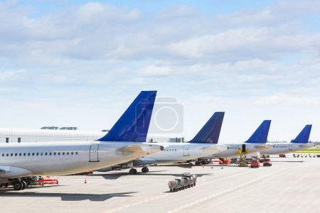Tails of some airplanes at airport during boarding operation
