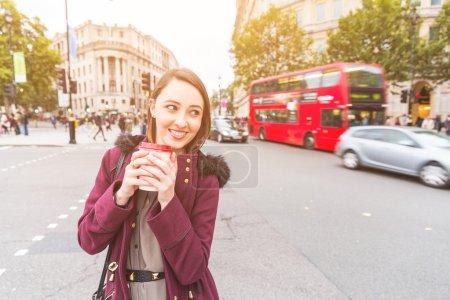 Photo pour Femme dans la position de Londres par une route très fréquentée, tenir le café. Elle est sur son milieu de la vingtaine et la recherche de caméra. Floue de trafic sur le fond. Concepts de voyages et de style de vie. - image libre de droit
