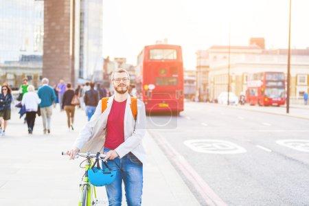 Photo pour Homme de hipster marchant sur le pont de Londres et tenant son vélo à pignon fixe. Il marche sur le trottoir, et il y a des gens et des autobus rouges sur fond. Concepts de mode de vie et transports. - image libre de droit