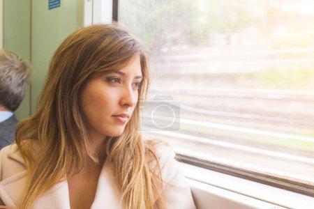 Photo pour Belle jeune femme regarde par la fenêtre du train. Elle est sur son la mi-vingtaine, mélangé le visage de la course, elle semble pensive et triste. Il y a un espace libre sur le droit d'ajouter du texte. Concept de voyage - image libre de droit