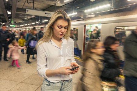 Photo pour Jeune femme, tapant sur un téléphone intelligent à la station de métro à Londres. Elle porte une chemise blanche et qu'elle cherche au téléphone. Il y a beaucoup de flous gens marchant sur la plate-forme et de monter à bord du train. - image libre de droit