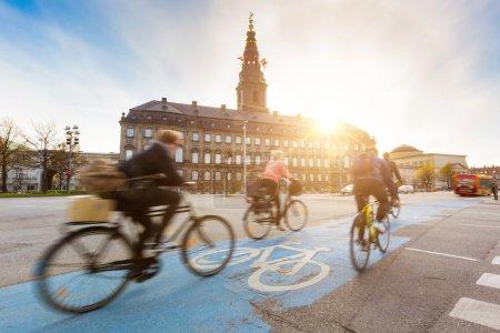 Photo pour Floues gens vont à vélo à Copenhague, avec le château de Christiansborg sur fond. Beaucoup de personnes préfère faire du vélo au lieu de prendre la voiture ou le bus pour se déplacer autour de la ville. Concept de mode de vie urbain. - image libre de droit