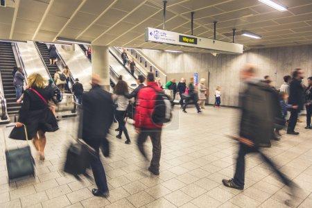 Blurred people walking inside train station