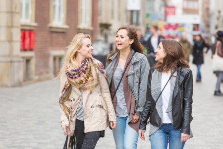 Photo pour Groupe de femmes marchant à Copenhague. Ils sont dans la vingtaine et ils portent des vêtements casual smart. Bonheur et concepts de l'amitié, ils sont souriants et à la recherche de l'autre. - image libre de droit