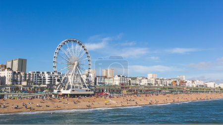 Photo pour Vue bord de mer de la jetée de Brighton. Prise de vue panoramique avec la célèbre grande roue, la plage de pierres avec méconnaissables personnes sur une journée d'été ensoleillée. - image libre de droit