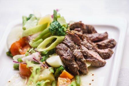 Photo pour Viande grillée avec légumes dans l'assiette, gros plan - image libre de droit